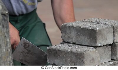 Construction worker cleaning bricks - construction worker is...