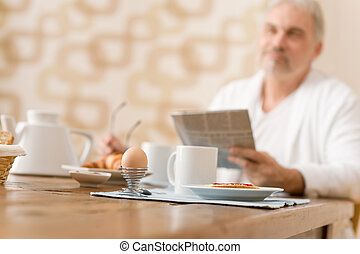 Senior mature man - breakfast at home with newspaper at desk
