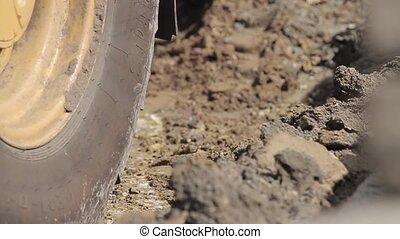 Digger shovels sand, roadworks
