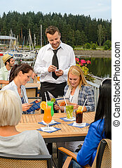 Waiter taking orders sidewalk bar from women - Waiter taking...