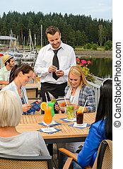 Waiter taking orders sidewalk bar from women - Waiter taking...