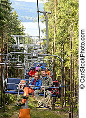 Young couple sitting on chairlift forest - Chairlift going...