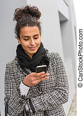 Happy woman sending text message on smartphone - Smiling...