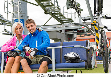 Young couple sitting chair lift waiting departing - Young...