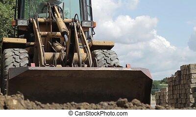 Digger shovels sand, roadworks - digger shovels sand,...
