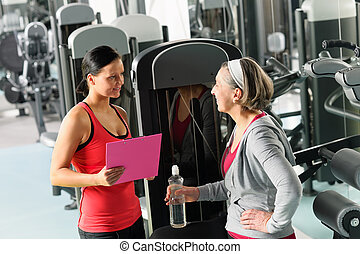 Personal trainer with senior woman at gym