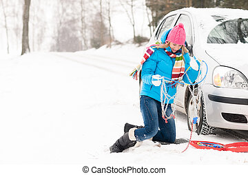 Woman with winter car tire chains snow - Woman with tire...