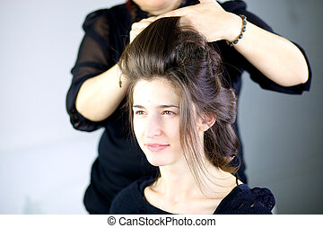 Beautiful female model getting hair done by professional...