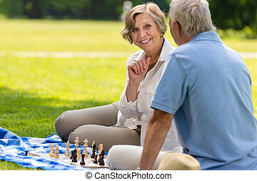 Senior wife and husband playing chess outdoors