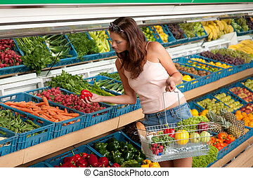 Grocery store shopping - Young woman buying vegetable in...