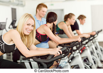 Young fitness people bike spinning with instructor