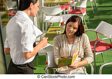 Woman order from waitress at cafe terrace - Woman deciding...