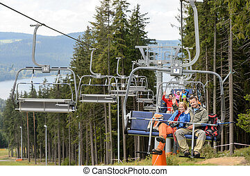 Waving young people sitting on chairlift going through...