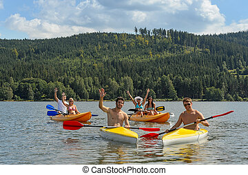 Waving cheerful friends in kayaks summer - Young kayaking...