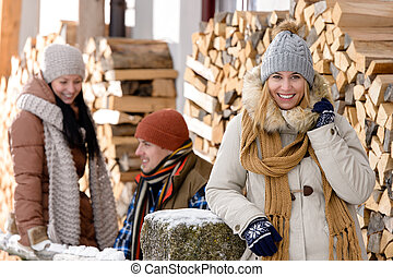 Young people outside winter cottage wooden logs countryside