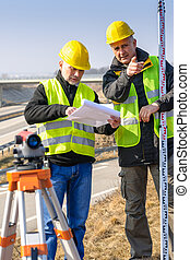 Geodesist read plans on construction site - Land surveyors...