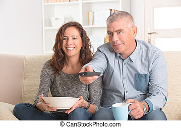 Couple watching tv in their living room - Cheerful mature...