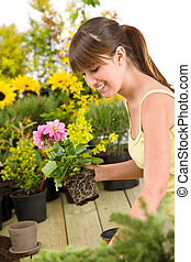 Gardening - smiling woman holding flower pot on white...