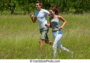 Young couple jogging outdoors in spring nature on sunny day