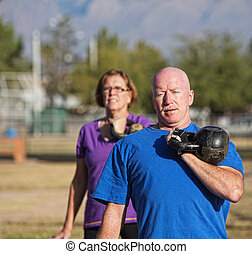 Athletic Mature Man Lifting Weights - Athletic middle aged...