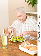 Senior mature man eat vegetable salad and white wine at...