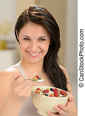 Attractive young woman eating bowl of cereal