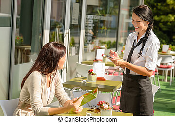 Waitress taking womans order at cafe bar menu smiling sunny