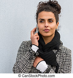 Woman in coat holding phone paying attention - Woman with a...
