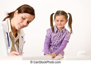 Female doctor write prescription for child at clinic