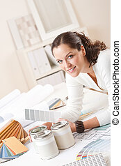 Young female interior designer at office with paint and...