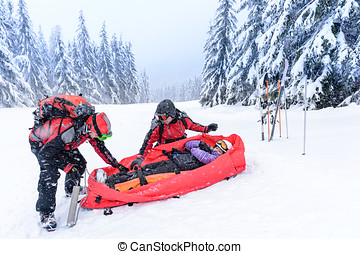 Ski patrol with rescue sled injured woman - Ski patrol with...
