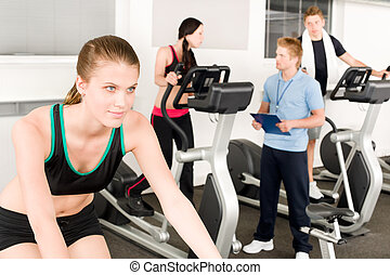 Young fitness woman doing spinning with instructor - Young...