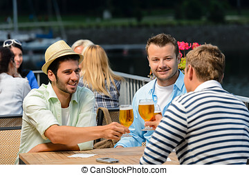 Three male friends drinking beer outdoor terrace - Three...