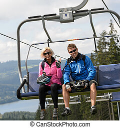 Young couple sitting on chairlift - Young smiling couple...