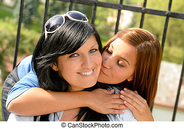 Daughter kissing her mother outdoors teen happy loving...