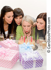 Birthday party - woman blowing candle on cake, champagne,...