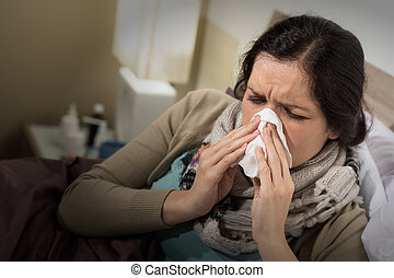 Woman having bad cold blowing her nose - Caucasian woman...