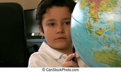 Boy studying with globe - Child looking at an desktop world...