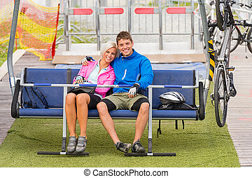 Cuddling couple sitting chair lift with bicycles - Cuddling...