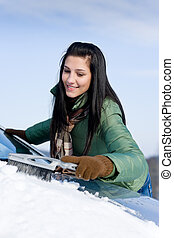 Winter car - woman remove snow from windshield with snow...