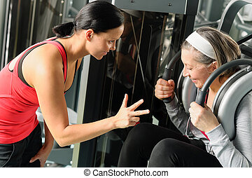 Personal fitness trainer with senior woman exercise