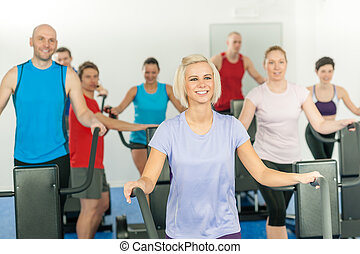 Fitness young group on elliptical cross trainer - Fitness...