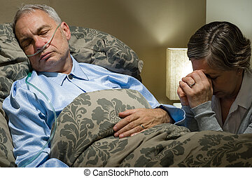 Senior woman praying for her sick husband lying in bed
