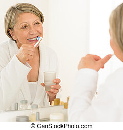 Senior woman brushing teeth bathroom mirror reflection -...