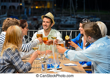 Young friends clinking glasses night restaurant - Group of...