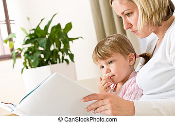 Mother with little girl read book together in lounge