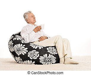 Elderly man sitting in armchair and drinking coffee