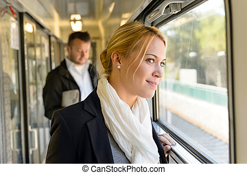 Woman in train looking pensive on window smiling travel...