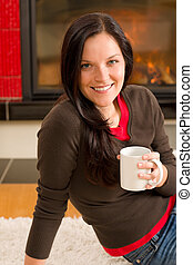 Winter home fireplace woman drink hot coffee - Young woman...