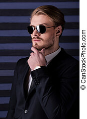 Always feeling confident. Side view of handsome young man in sunglasses and formalwear holding hand on chin and looking away while standing against striped background